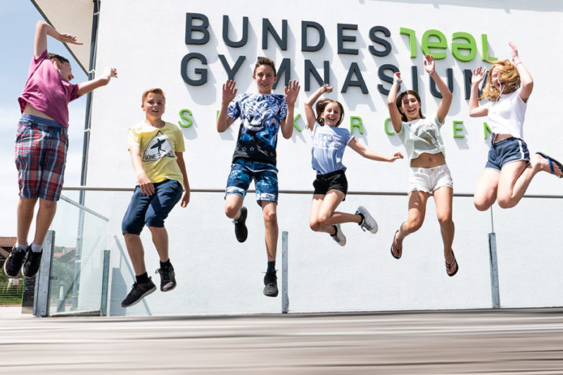 hüpfende Schüler*innen vor dem Gymnasium Seekirchen